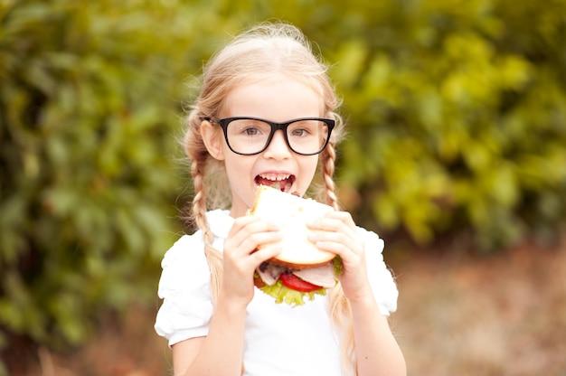 Grappig kindmeisje dat buiten sandwich eet