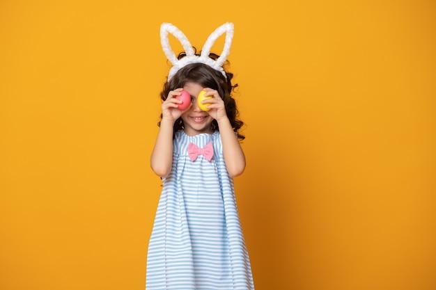 Grappig kindmeisje dat konijntjesoren draagt en een kleurrijk paasei voor haar oog op gele achtergrond steunt.