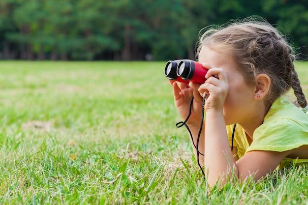 Grappig kindmeisje die door verrekijkers op zonnige de zomerdag kijken