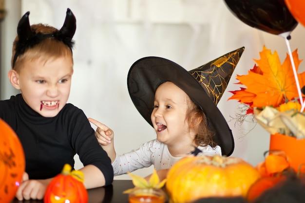 Grappig kindmeisje en tienerjongen in heks en kwade kostuums voor halloween-partij
