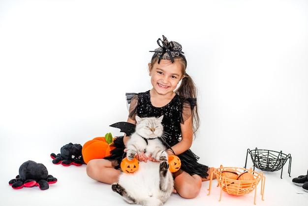Grappig kindmeisje in een heksenkostuum voor halloween met een kat in een pak in haar handen