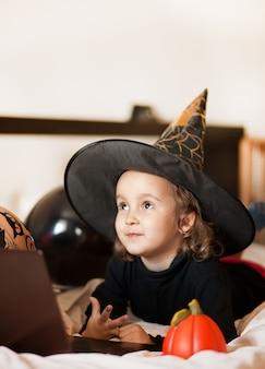 Grappig kindmeisje in heksenkostuum voor halloween met behulp van een digitaal tabletlaptop notitieboekje. bel vrienden of ouders online.