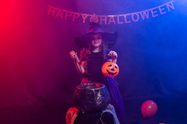 Grappig kindmeisje in heksenkostuum voor halloween met pompoen jack.