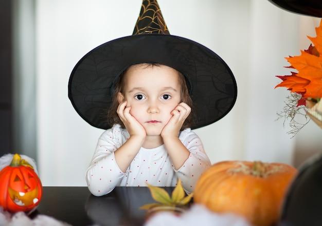 Grappig kindmeisje in heksenkostuum voor halloween.
