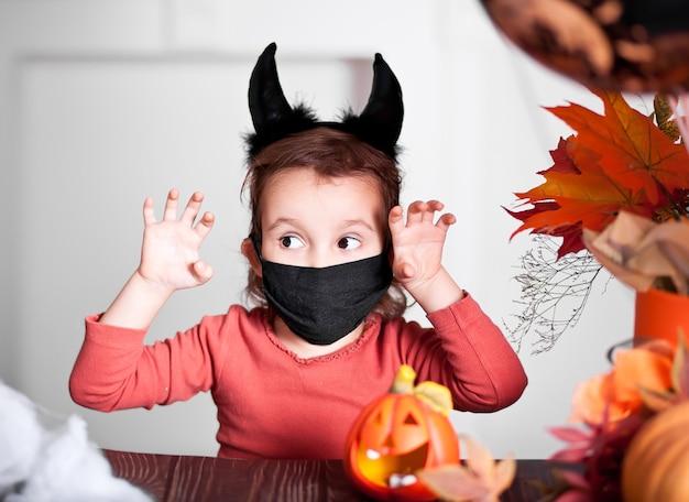 Grappig kindmeisje in kwaad kostuum voor halloween.