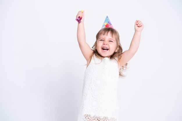 Grappig kindmeisje in witte kleding en verjaardagshoed die in fluitje op witte muur blazen