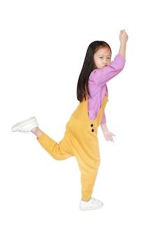 Grappig klein aziatisch kindmeisje in het roze-geel tuinbroek springen
