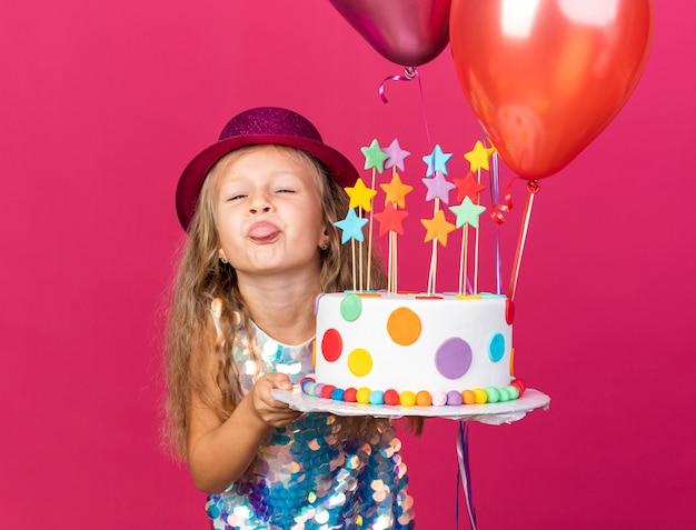 Grappig klein blond meisje met paarse feestmuts steekt tong uit met heliumballonnen en verjaardagstaart geïsoleerd op roze muur met kopieerruimte