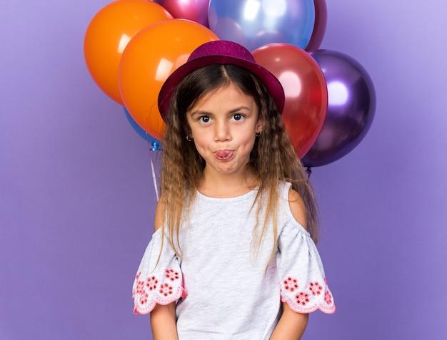 Grappig klein kaukasisch meisje met violet feestmuts steekt tong uit staande voor heliumballonnen geïsoleerd op paarse muur met kopieerruimte