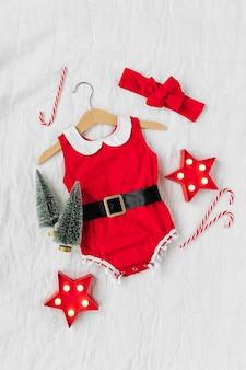 Grappig klein kerstmankostuum voor babymeisje op bed. vrolijk kerstfeest.