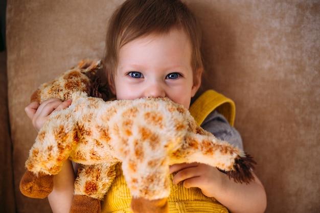 Grappig klein kind heeft plezier bij het spelen met zacht speelgoed op de bank thuis