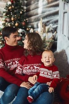 Grappig klein kind in een lelijke trui die met zijn ouders poseert tijdens het kerstinterieur. jonge ouders en hun zoontje in kerstkleren