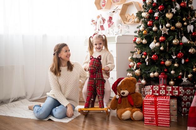 Grappig klein kind plezier met haar moeder thuis in de buurt van de kerstboom