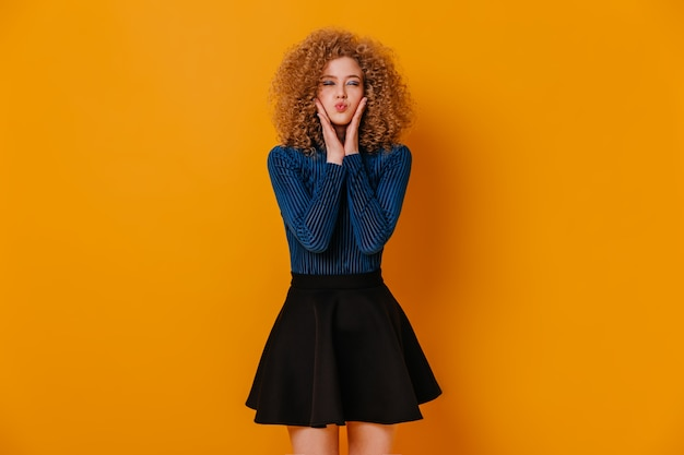 Grappig krullend meisje in blauwe trui en zwarte rok blies haar wangen uit op gele ruimte.