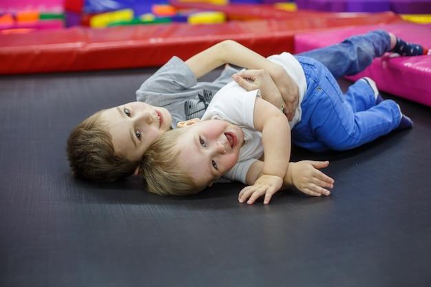Grappig lachende kinderen op trampoline. oudere broer omarmt de jongere. actieve rust in het kindercentrum. jongens speelt in de speelkamer. kleine vrienden hebben plezier in de speelkamer. vriendschap van twee broers