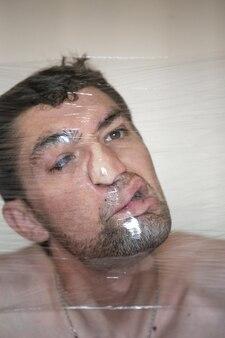 Grappig mannelijk gezicht, vervorming door plastic verpakkingen