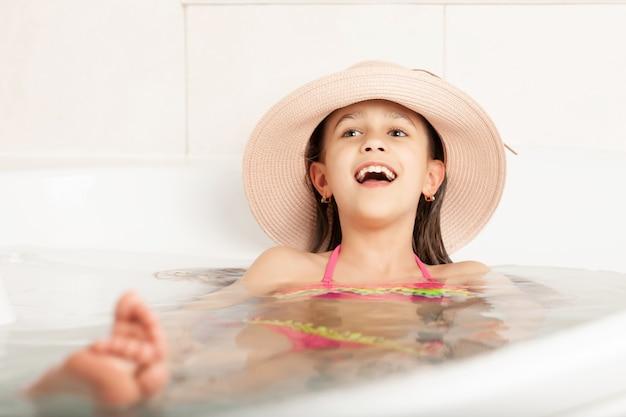 Grappig meisje baadt in de badkamer