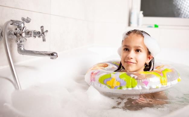 Grappig meisje baadt in een badkuip met een opblaasbare reddingsboei en met schuim in het water
