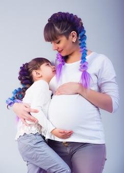 Grappig meisje dat aan de zwangere buik luistert