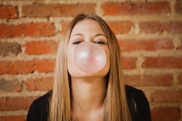 Grappig meisje dat een pruim met een kauwgom maakt