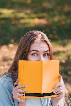 Grappig meisje dat haar gezicht verbergt onder een notitieboekje