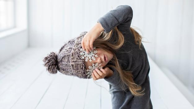 Grappig meisje dat haar ogen bedekt met sneeuwvlokken