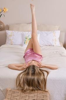 Grappig meisje dat hals over kop op rug ligt met haar naar beneden en benen omhoog