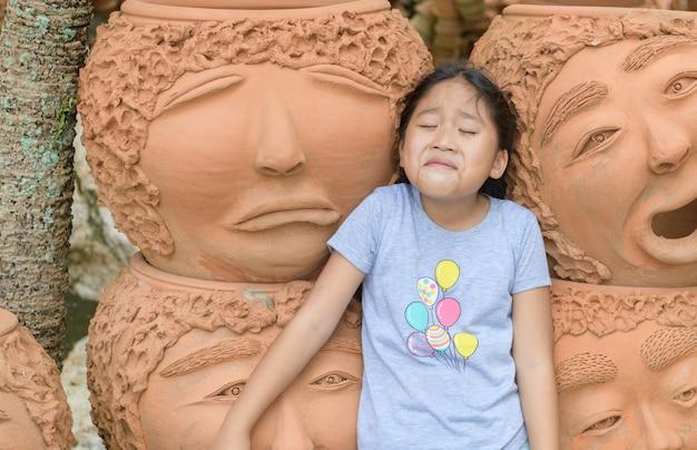 Grappig meisje dat huilende of droevige emotie toont in de buurt van kleipotten,