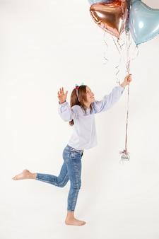 Grappig meisje dat met kattenoren ballons houdt. concept verjaardag