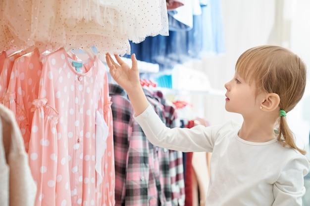 Grappig meisje dat mooie roze kleding in opslag bekijkt