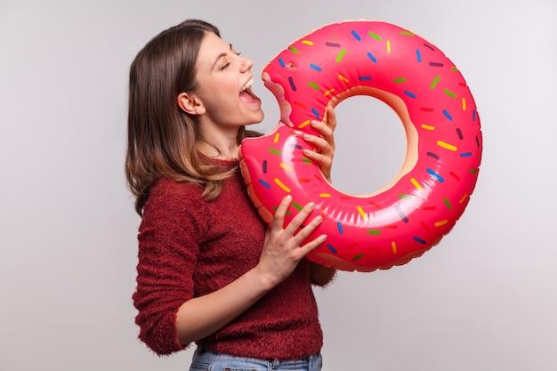 Grappig meisje dat opblaasbare grote donut bijt, doet alsof ze een rubberen ring eet, plezier heeft op zomervakantie