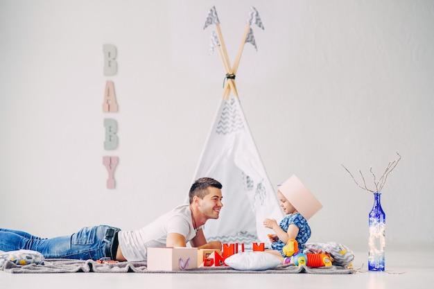 Grappig meisje dat pret in de ruimte van de witte kinderen heeft. het gelukkige meisje spelen met haar vader.