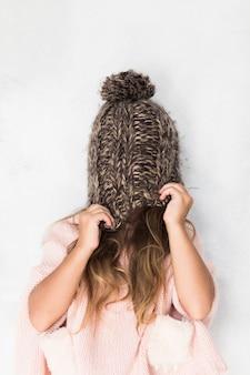 Grappig meisje die haar gezicht behandelen met de winterhoed