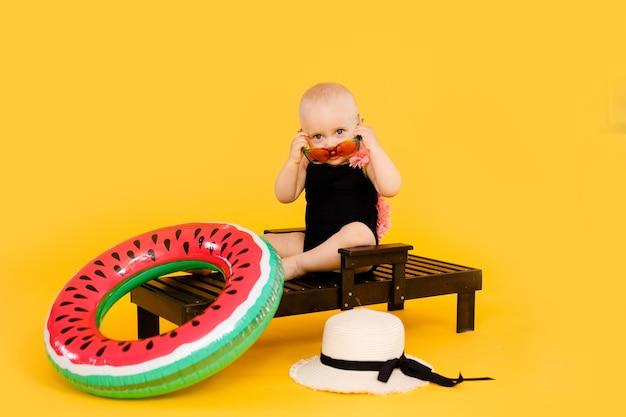 Grappig meisje gekleed in een zwart en roze zwembroek, grote hoed en zonnebril zittend op houten strandstoel geïsoleerd op geel