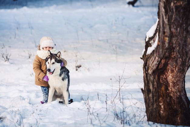 Grappig meisje haar grote malamute-hond knuffelen in de winter in het bos