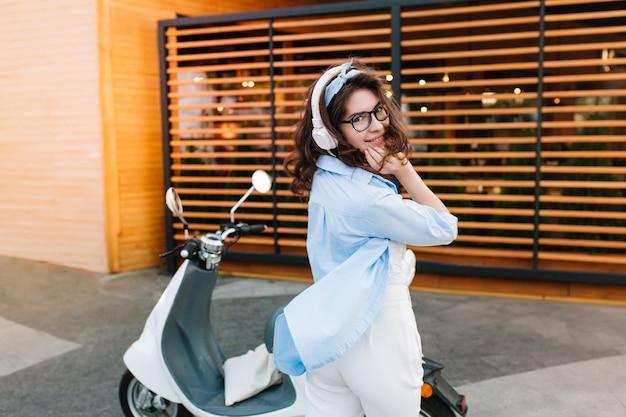 Grappig meisje in blauw oversized overhemd speels poseren op straat genieten van muziek in witte koptelefoon