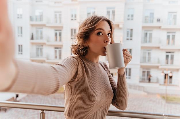Grappig meisje in bruine trui koffie drinken op balkon. aantrekkelijke jonge vrouw selfie met kopje thee maken.