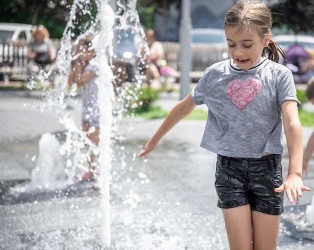 Grappig meisje in een fontein, tussen de spatten van water op een hete zomerdag.