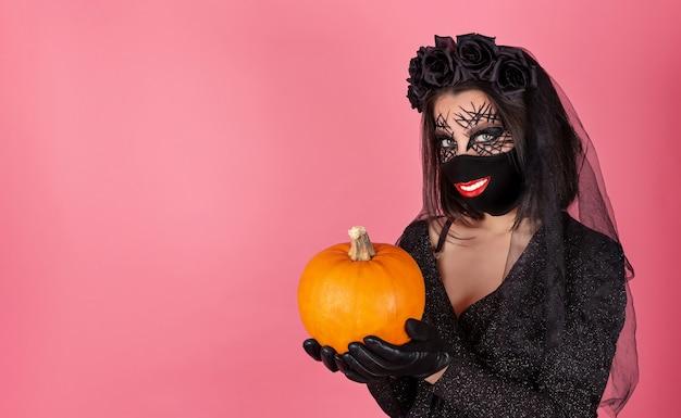 Grappig meisje in een halloween-kostuum met een glimlachprint op een zwart masker en een pompoen in haar handen