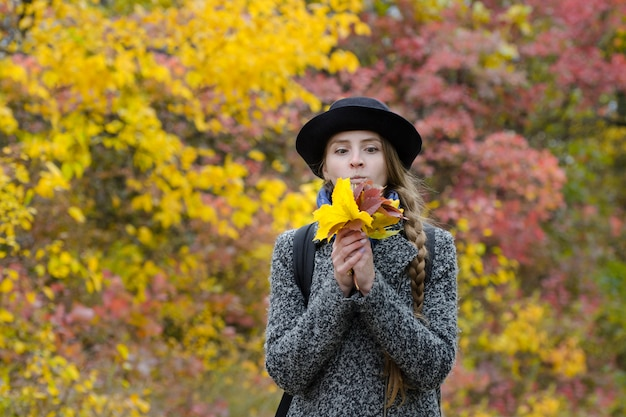 Grappig meisje in een hoed met een boeket van herfstbladeren.
