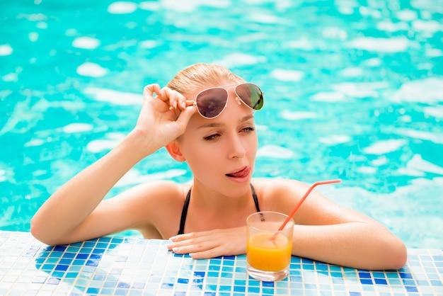 Grappig meisje in een pool met sap en glazen die tong tonen