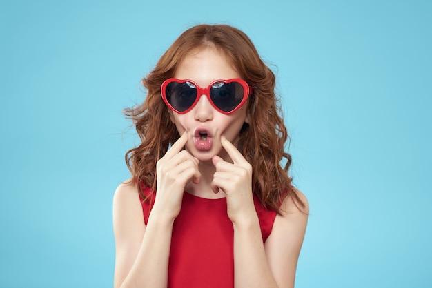 Grappig meisje in een rode jurk op blauwe achtergrond