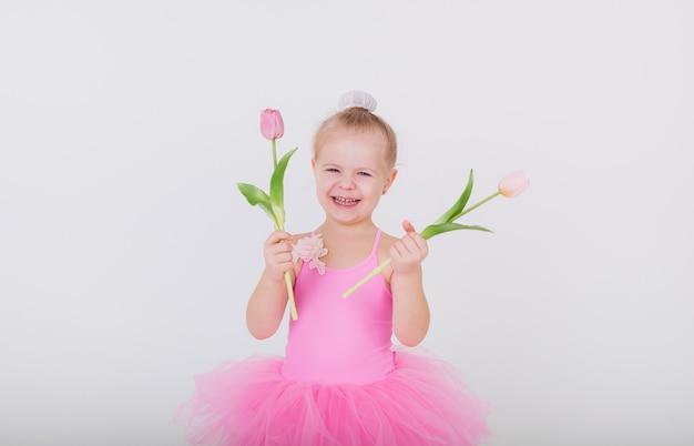 Grappig meisje in een roze jurk met tulpen op een witte muur