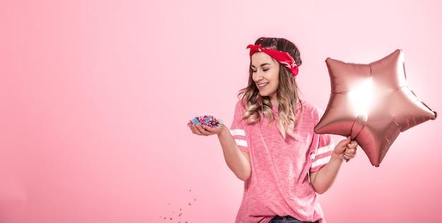 Grappig meisje in een roze t-shirt met ballonnen en confetti geeft een glimlach en emoties op een roze achtergrond