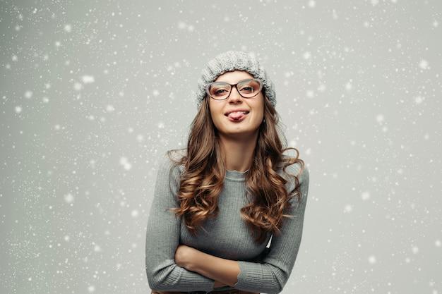 Grappig meisje in grijze slijtage die tong tonen bij camera.