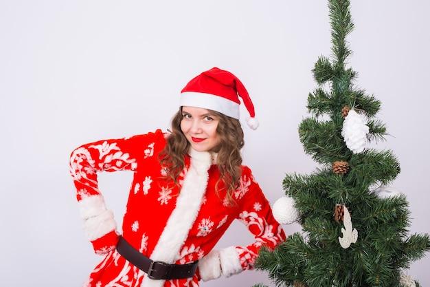 Grappig meisje in het dragen van xmas santa kostuum in de buurt van kerstboom.