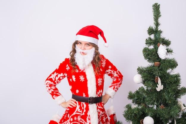 Grappig meisje in het dragen van xmas santa kostuum over kerstboom