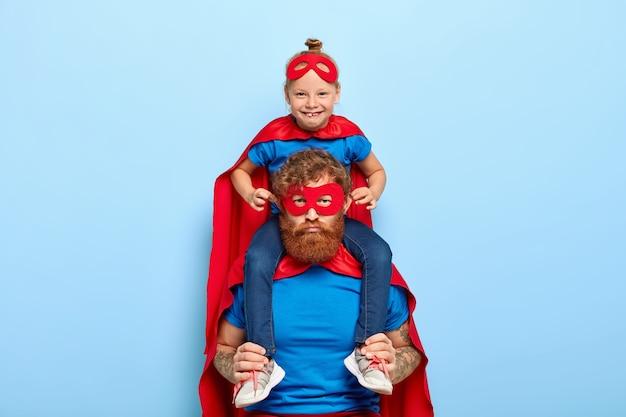 Grappig meisje in superheld kostuum, zit op vaders schouders, laat zijn oren uitsteken, heeft plezier met papa