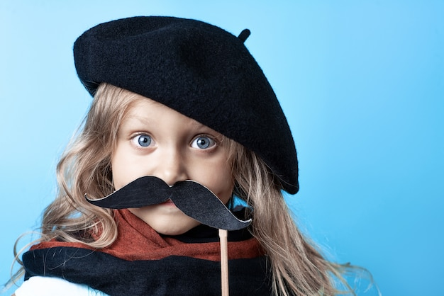 Grappig meisje in zwarte baret, sjaal en snor op een stok op blauw