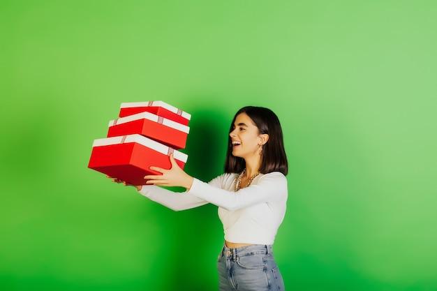 Grappig meisje is drie rode geschenkdozen overgeven, geïsoleerd op groen oppervlak.